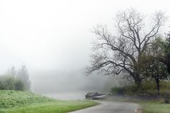 Curvy road in autumn mist with an old shabby house under a bare tree, gray rural landscape in the country, dangerous fog weather f Royalty Free Stock Photo