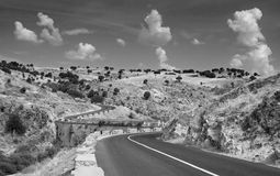Curvy road crossing the valley. Black and white. Unusual sky and cloud formations Stock Image