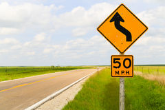 Curvy Road in the Flint Hills. Road signs displaying the maximum speed of 50 mph and that it is a curvy road in the Flint Hills region in Kansas Stock Images