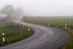 Curvy road in a foggy weather Royalty Free Stock Photo