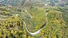 Curvy road in green forest, low hills. Slovakia. Autumn nature. Stock Photo