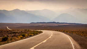 Curvy road leading to the mountain Stock Photography