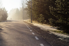 Curvy road with man silhouette on sunny morning Stock Photos
