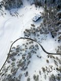 A curvy road through the mounatin and forest. And snow field with cross-country ski run in winter stock photos
