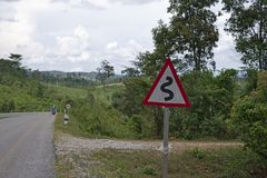 Curvy Road Sign In Laos. Curvy road sign in the Nakai highlands along the Konglor Loop with distant scooter rider royalty free stock image