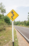 Curvy road sign to the mountain in rural area Stock Image