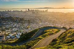 Curvy road and view of downtown at sunrise from Twin Peaks  Stock Images
