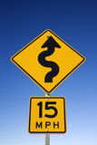 Curvy Road Warning Sign. With second sign saying 15 mph. Vertical shot royalty free stock photo