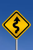 Curvy road warning sign. Over blue sky royalty free illustration