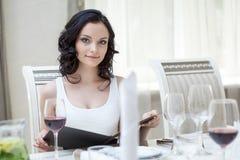 Curvy slender brunette sitting at restaurant table Stock Image
