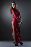 Curvy smiling woman posing in red long dress Royalty Free Stock Photography
