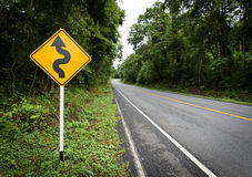 Curvy vägmärke till berget i landsbygd Fotografering för Bildbyråer