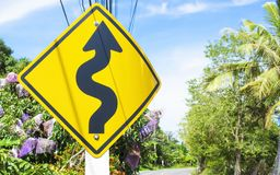 Curvy Verkehrsschild zum Berg im ländlichen Gebiet stockfotos
