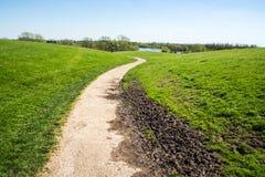 Curvy Weg mit etwas Schlamm in der hügeligen Landschaft am sonnigen Tag lizenzfreies stockfoto
