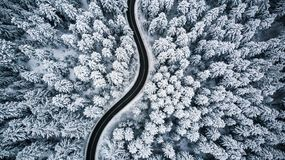 Curvy windy road in snow covered forest, top down aerial view.  stock photography