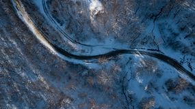 Curvy windy road in snow covered forest, top down aerial view. royalty free stock photography