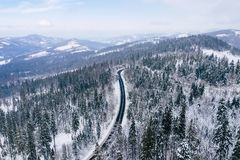Curvy windy road in snow covered forest, top down aerial view. Winter landscape.  royalty free stock photo