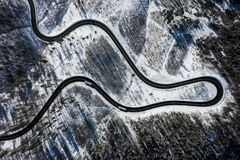 Curvy windy road in snow covered forest, top down aerial view. Winter landscape.  stock photo