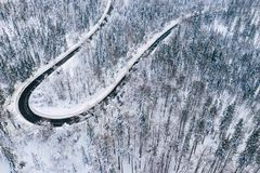 Curvy windy road in snow covered forest, top down aerial view. Winter landscape.  royalty free stock image