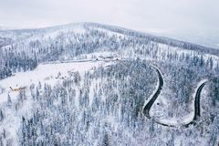 Curvy windy road in snow covered forest, top down aerial view. Winter landscape.  stock images