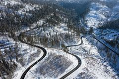 Curvy windy road in snow covered forest, top down aerial view. Winter landscape.  royalty free stock photos