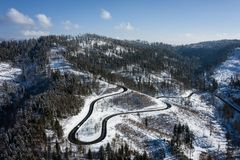 Curvy windy road in snow covered forest, top down aerial view. Winter landscape.  royalty free stock images