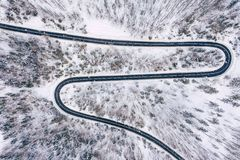 Curvy windy road in snow covered forest, top down aerial view. Winter landscape.  stock image