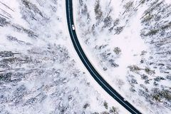 Curvy windy road in snow covered forest, top down aerial view. Winter landscape.  royalty free stock photography