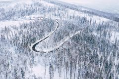 Curvy windy road in snow covered forest, top down aerial view. Winter landscape stock image