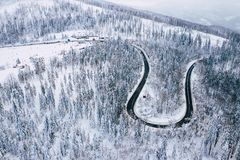Curvy windy road in snow covered forest, top down aerial view. Winter landscape.  stock photography