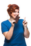 Curvy woman eating chocolate. Tablet on the white background Royalty Free Stock Image