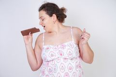 Curvy woman in funny pajamas with a chocolate bar stands on a white background in the Studio. Isolated stock photo