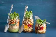 Cuscús y ensalada de pasta del vegano en tarros de albañil con bea de las verduras Imagenes de archivo