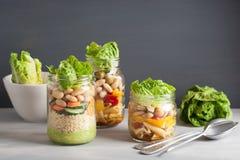 Cuscús y ensalada de pasta del vegano en tarros de albañil con bea de las verduras Foto de archivo