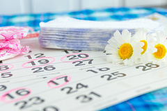 Cuscinetti sanitari, calendario, asciugamano e fiore rosa su fondo leggero Fotografia Stock