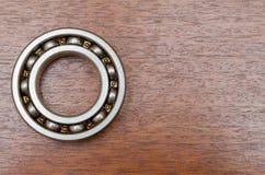 Cuscinetti a sfera d'acciaio sulla tabella di legno Immagine Stock