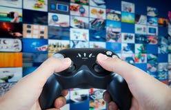 Cuscinetto del gioco della tenuta del Gamer in mani Regolatore del gioco del gioco con il flusso continuo delle multimedia immagine stock