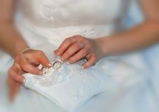 Cuscinetto del pizzo della tenuta della sposa con due fedi nuziali dell'oro Fotografia Stock Libera da Diritti