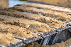 Cuscinetto di brontolone del metallo di un escavatore indurito con sporcizia immagini stock libere da diritti