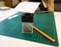 Cuscinetto di gomma, matita e tagliatore sulla tavola di tha Fotografia Stock