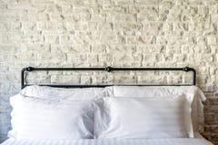 Cuscini bianchi su una camera da letto classica con il muro di mattoni bianco Immagine Stock