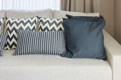 Cuscini in bianco e nero sul sofà beige di colore Fotografie Stock