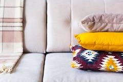 Cuscini e plaid sulla fine beige del sofà su con lo spazio della copia S Fotografia Stock Libera da Diritti