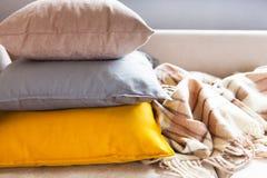 Cuscini e plaid sulla fine beige del sofà su con lo spazio della copia S Immagini Stock Libere da Diritti