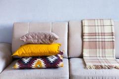 Cuscini e plaid sulla fine beige del sofà su con lo spazio della copia S Immagini Stock