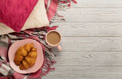 Cuscini e plaid tricottato, croissant e caffè su un legno leggero fotografia stock