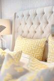 Cuscini gialli con un'arte del labirinto sul primo piano del letto Fotografia Stock