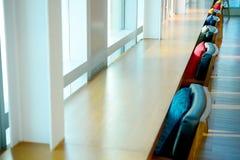 Cuscini grigi gialli blu rossi che mettono su una sedia vicino al windo immagine stock