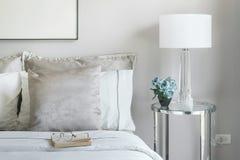 Cuscini grigio chiaro e bianchi sul letto con il barattolo del fiore sul comodino fotografia stock