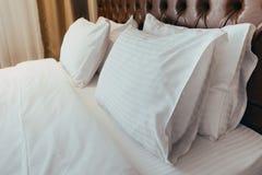 Cuscini molli comodi sul letto Strati e cuscino bianchi della lettiera del primo piano sul fondo leggero della stanza della paret immagini stock libere da diritti